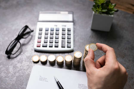Person Doing Calculation With Stacked Coins On Desk