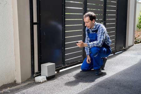 Repairman Fixing Broken Automatic Door In Building