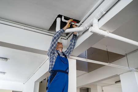 Plumber Repairing Water Pipes In Residential Building