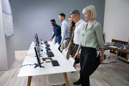 Group Of Happy Young Businesspeople Doing Stretching Exercise In Office