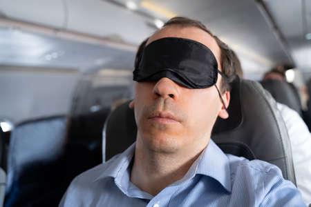 Young Man Sleeping With Sleep Mask On Airplane Stock Photo