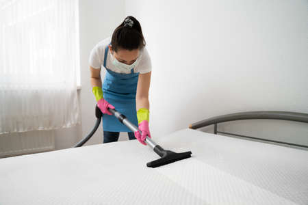 Mattress Cleaning Professional Service By Female Cleaner Using Vacuum Cleaner