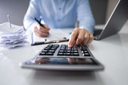 Cropped Image Of Businessman Calculating Expense At Desk In Office Banque d'images