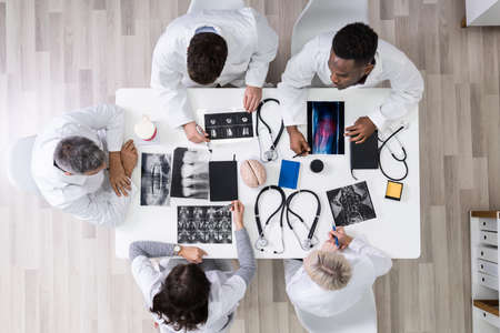 Doctors And Radiologists Discussing X-ray Images Of Patient Stock Photo