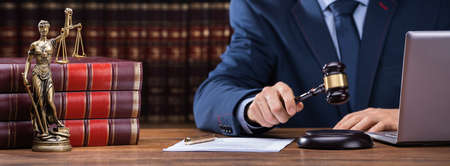 Midsection Of Judge Striking Gavel Near Mallet And Laptop At Desk In Courtroom Stock Photo