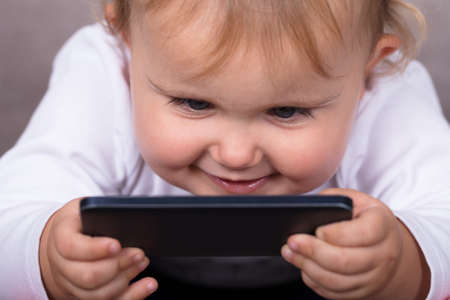Little Girl With Mobile Phone At Home Stock Photo