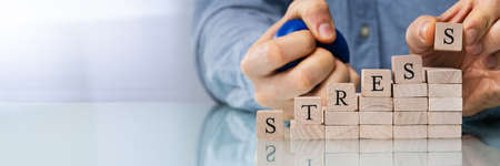 Close-up Of Persons Hand Placing Last Alphabet Of Word Stress On Wooden Block