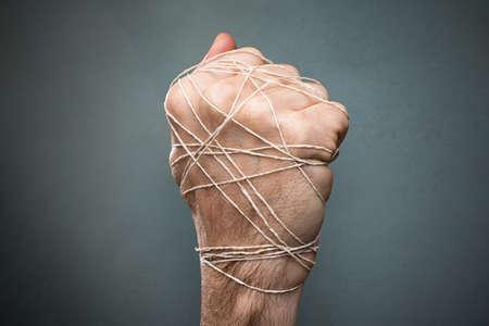 Man Hand Tied With Wire On Dark Background