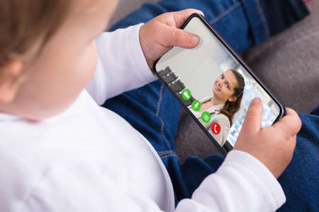 Girl Video Chatting With Mother On Smartphone In House Stock Photo