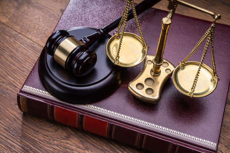 Wooden Gavel With Golden Scale Near Book On Table