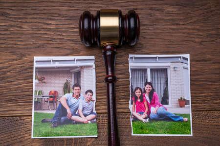Family Photo Torn In Half Near Judge Gavel On The Wooden Desk