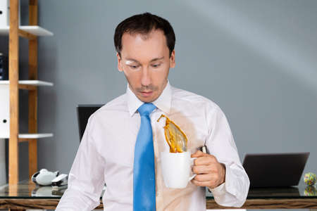 Man Spilling Coffee On On His Shirt In Office Stock Photo