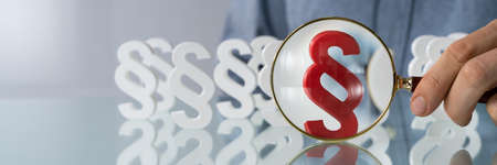 Close-up Of Businessmans Hand Looking Red Paragraph Sign With Magnifying Glass On Wooden Desk