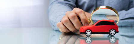 Person Scrutinizing A Car Model Using Magnifying Glass On Desk