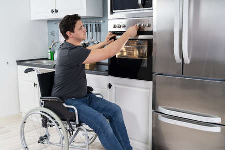 Disabled Man Using Microwave Oven For Baking In Kitchen