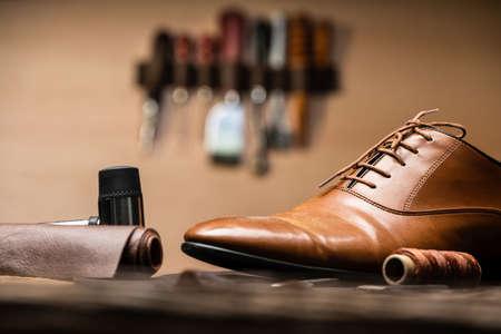 Shoemaker Tools And Finished Shoe On Desk