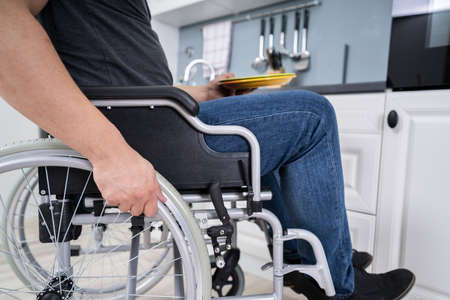 Handicapped Man Sitting On Wheelchair In Kitchen Holding Dishes