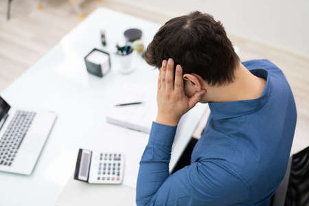 Tensed Young Businessman Calculating Tax At Desk In Office Stockfoto