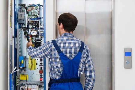 Technician Repairing Control Panel Of Broken Elevator