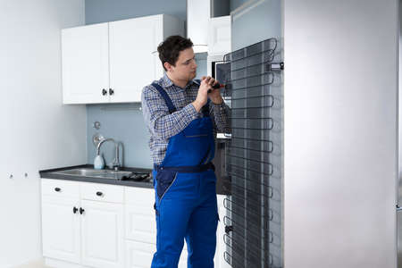 Male Worker Repairing Refrigerator With Screwdriver In House