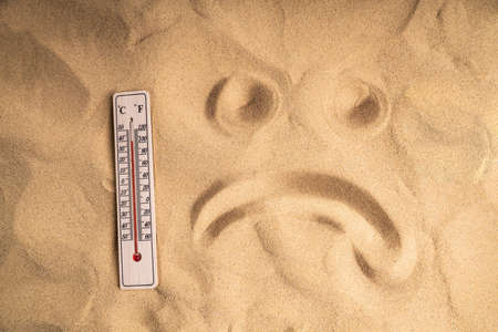Close-up Of Thermometer With High Temperature On Sand And Sad Face