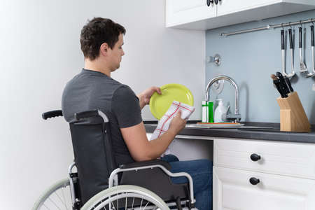 Handicapped Man Sitting On Wheelchair Washing And Cleaning Dishes In Kitchen