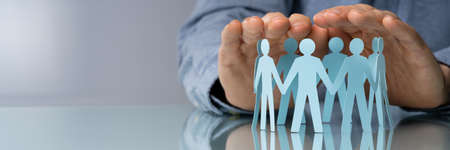 Close-up Of A Businessperson's Hand Protecting Cut-out Figures On Desk Stock Photo