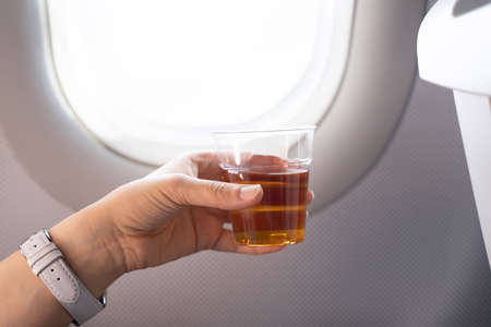 Holding Alcoholic Drink In Front Of Window In Airplane Foto de archivo