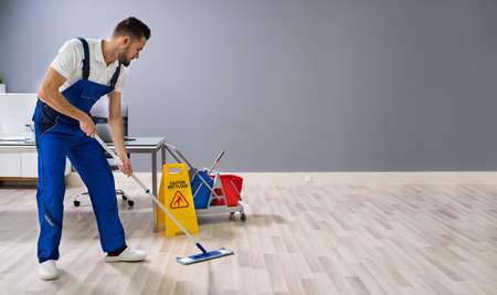 Man With Mop And Wet Floor Sign Imagens