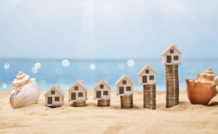 House Models Arranged On Stacked Coins At Sunny Beach Standard-Bild