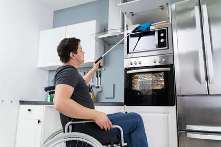 Disabled Man Using Grabber Tool To Grab Potholders In Kitchen