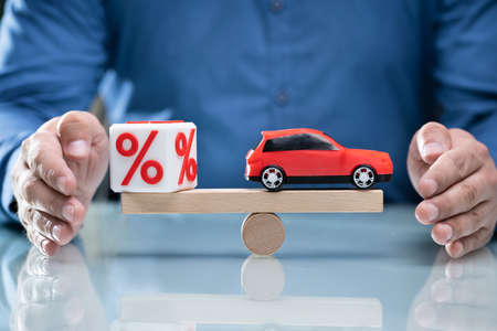 Businessperson's Hand Protecting Balance Between Cubic Block With Percentage Symbol And Blue Car