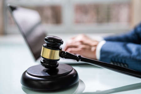 Close-up Of A Businessperson's Hand Using Laptop With Gavel On Desk Stock Photo