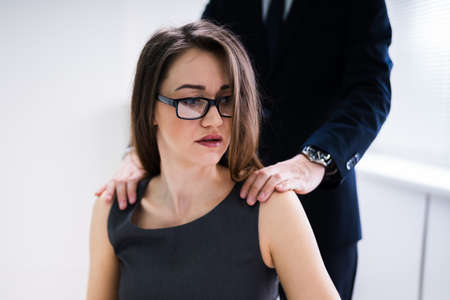 A Boss Touching The Shoulder Of Female Colleague In Workplace At Office Foto de archivo