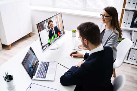 Two Young Businesspeople Video Conferencing On Computer At Office