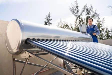 Male Plumber Doing Solar Energy Boiler Inspection Stockfoto