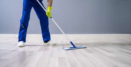 Worker Mopping Floor With Mop In Office Foto de archivo
