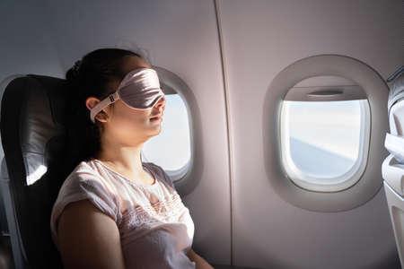 Young Woman Sleeping With Sleep Mask On Airplane Standard-Bild