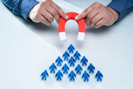 Businessman's Hand Attracting Blue Team With Horseshoe Magnet On White Background Banque d'images