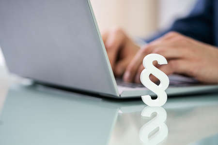 Businessperson's Hand Using Laptop With Paragraph Symbol On Desk Stock Photo