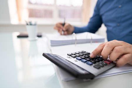 Cropped Image Of Businessman Calculating Invoice At Desk Archivio Fotografico