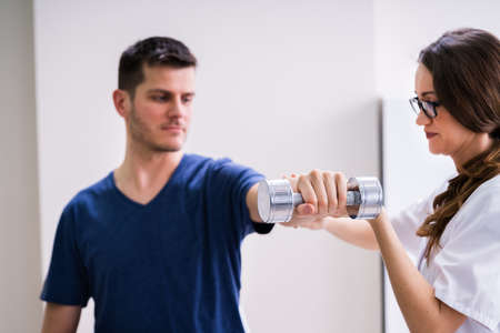 Therapist Assisting Male Patient While Exercising With Dumbbell