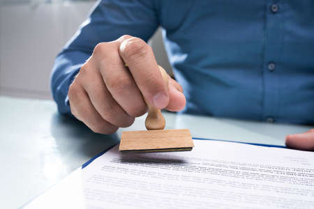 Close-up Of Businessman Hand Using Stamper On Document Stock Photo