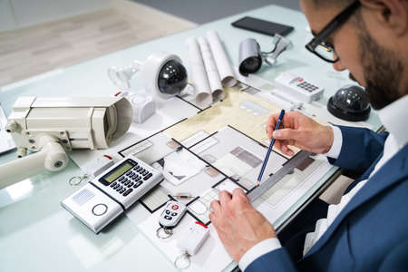 Architect Drawing Blueprint With Various Security Equipment On Desk Foto de archivo