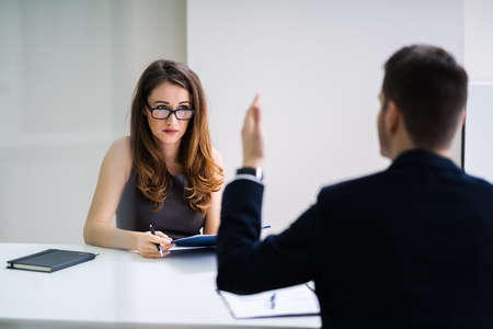 Close-up Of Businessperson Quarreling To Young Businesswoman At Desk