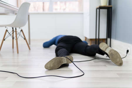 An Elevated View Of Man Stumbling With An Electrical Cord