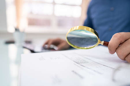 Close-up Of Businessperson Hand Examining Bills With Magnifying Glass At Desk Banco de Imagens