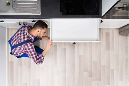 Close-up Of A Young Male Carpenter Installing Drawer With Screwdriver