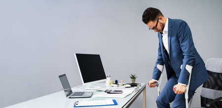 Man With Broken Leg Using Crutches To Get Up From Chair In Office