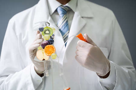 Male Doctor Holding Saline Bag With Fruit Slices Inside In Hospital 写真素材